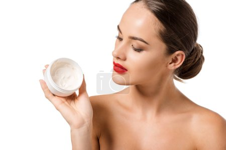 attractive girl with red lips looking at jar with face cream isolated on white