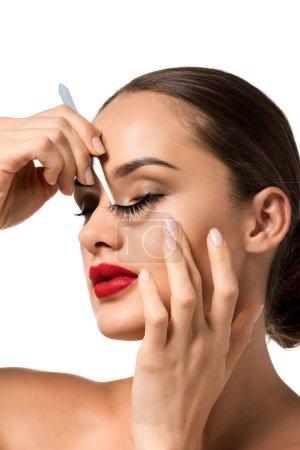 close up view of beautiful girl keeping false eyelashes with tweezers isolated on white