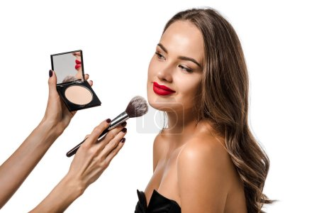 Foto de Vista recortada de mujer aplicando polvo con cepillo cosmético en la cara de chica atractiva aislada en blanco - Imagen libre de derechos
