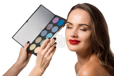 Photo for Cropped view of woman holding palette with eyeshadows and making up beautiful girl with closed eyes isolated on white - Royalty Free Image