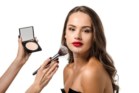 Photo for Cropped view of woman applying powder with cosmetic brush on face of beautiful model looking at camera isolated on white - Royalty Free Image