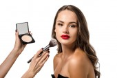 cropped view of woman applying powder with cosmetic brush on face of beautiful model looking at camera isolated on white