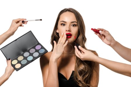 Photo pour Vue recadrée de femmes occupant des rouge à lèvres liquide, brosse cosmétiques et palettes à fards à paupières et surprise fille isolé sur blanc - image libre de droit