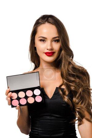 Photo pour Belle fille en robe noire avec lèvres rouges tenant palette avec fards à paupières, regardant caméra et souriant isolé sur blanc - image libre de droit