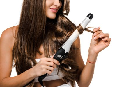 cropped view of girl with long brown hair using curling iron isolated on white