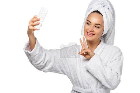 Photo pour Jolie fille en peignoir montrant le symbole de paix et de la prise de selfie isolé sur blanc - image libre de droit