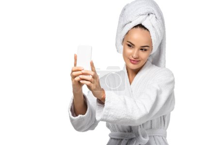 attractive girl in bathrobe with towel on head taking selfie isolated on white