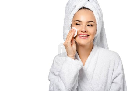 attractive girl in bathrobe cleaning face with cotton sponge and smiling isolated on white