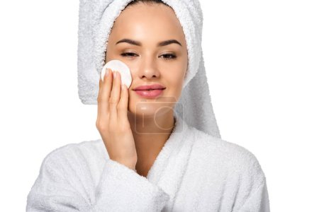 Photo for Close up view of attractive girl in bathrobe cleaning face with cotton sponge and looking at camera isolated on white - Royalty Free Image
