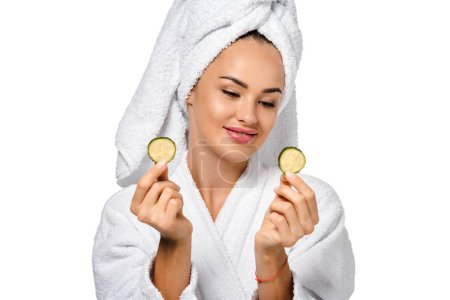 Photo for Attractive girl in bathrobe looking at cucumber slices and smiling isolated on white - Royalty Free Image