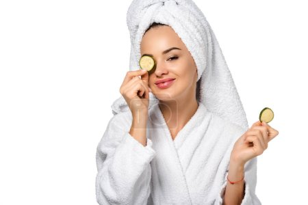 beautiful girl in bathrobe holding cucumber slice near eye and smiling isolated on white