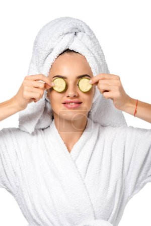 beautiful girl in bathrobe holding cucumber slices near eyes and smiling isolated on white