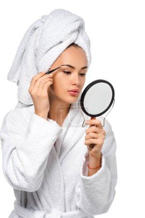 schöne Mädchen im Bademantel mit Blick auf Spiegel und Pinzette Augenbrauen isoliert auf weiß