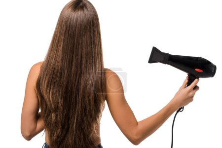 back view of girl with long brown hair holding hair dryer isolated on white