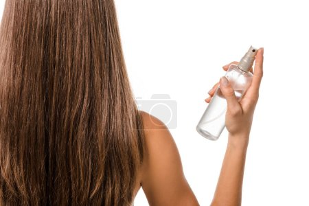 back view of girl with long brown hair holding hair spray isolated on white