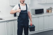 partial view of bearded repairman in working overall holding toolbox and showing thumb up in kitchen at home