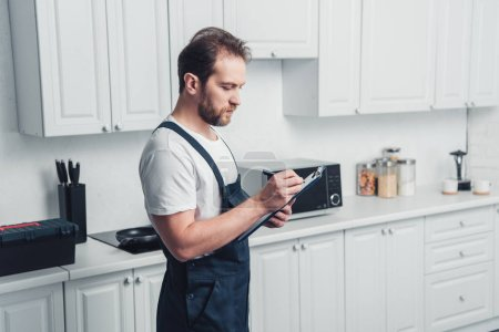 Photo for Adult repairman in working writing in clipboard in kitchen at home - Royalty Free Image