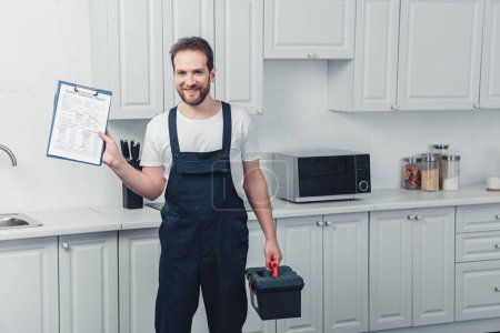 Photo for Smiling bearded repairman in working overall showing clipboard in kitchen at home - Royalty Free Image