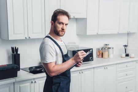 Photo pour Adulte beau barbu réparateur avec presse-papiers dans cuisine - image libre de droit