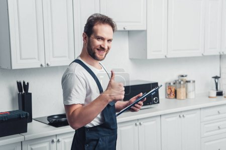 Photo for Smiling handsome adult bearded repairman holding clipboard and doing thumb up gesture in kitchen - Royalty Free Image