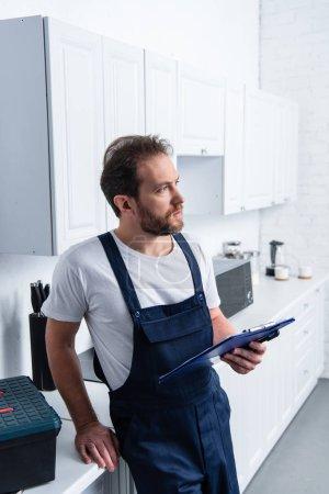 Photo pour Cher réparateur barbu adulte avec presse-papiers dans la cuisine à la maison - image libre de droit