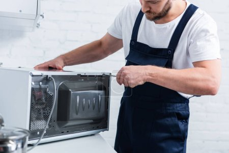 Photo for Partial view of bearded handyman repairing microwave oven by screwdriver in kitchen - Royalty Free Image