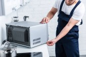 partial view of adult handyman repairing microwave oven in kitchen