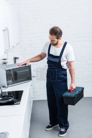 high angle view of adult handyman with toolbox checking microwave oven in kitchen
