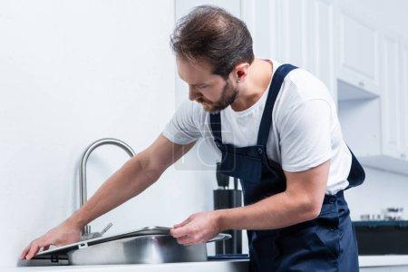 Photo pour Adulte barbu réparateur en travaillant évier de fixation globale dans la cuisine - image libre de droit