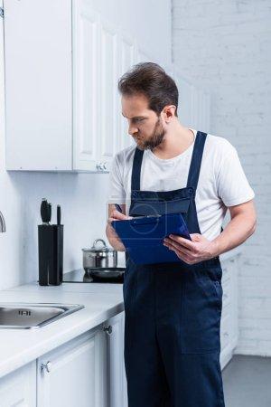 Photo pour Réparateur adulte sérieux dans l'écriture globale de travail dans le presse-papiers et le contrôle évier dans la cuisine - image libre de droit