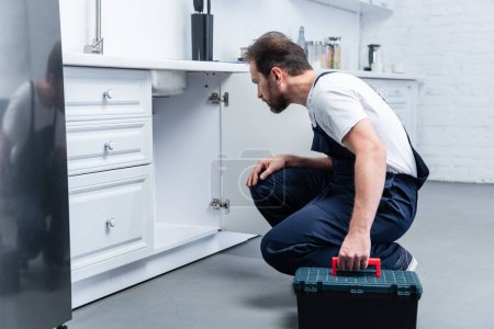 Photo for Side view of adult bearded repairman with toolbox checking sink in kitchen - Royalty Free Image