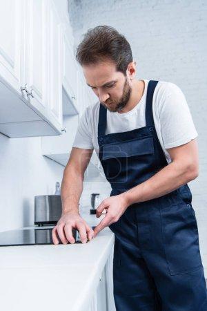 Photo pour Concentré de bricoleur en travaillant ensemble fixation four dans cuisine - image libre de droit