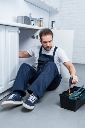 Photo for Handyman in working overall fixing oven and taking tools from toolbox in kitchen - Royalty Free Image