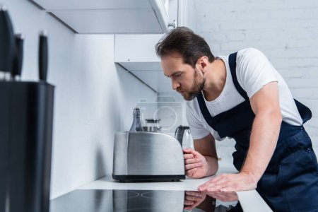 Photo for Serious handyman in working overall fixing toaster in kitchen - Royalty Free Image