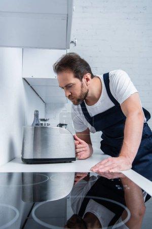 Photo pour Concentré artisan barbu dans le travail global de fixation grille-pain dans la cuisine - image libre de droit