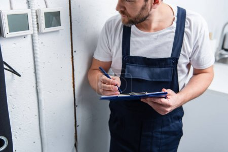 cropped image of adult electrician with clipboard checking electrical panel