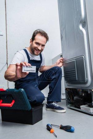 Lächelnder erwachsener Handwerker zeigt Karte mit Schriftzug bei Hausbesichtigung, während er neben kaputtem Kühlschrank sitzt