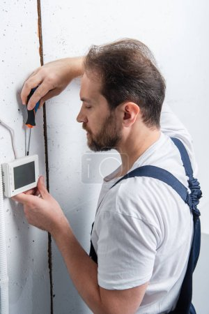 male electrician with clipboard fixing electrical box by screwdriver