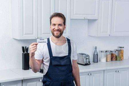 Photo pour Sourire masculin bricoleur à travailler ensemble carton avec lettrage inspection à la maison - image libre de droit