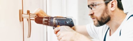 panoramic view of focused male handyman in goggle repairing window handle with electric drill