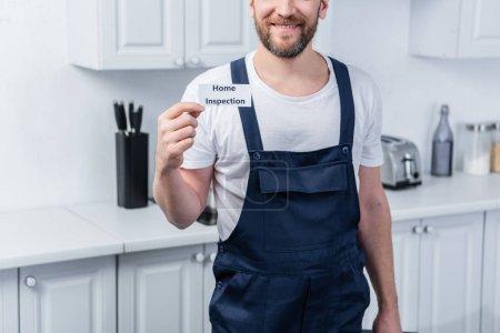 Photo pour Plan recadré de homme bricoleur tenant boîte à outils et montrant la carte avec lettrage inspection à domicile - image libre de droit