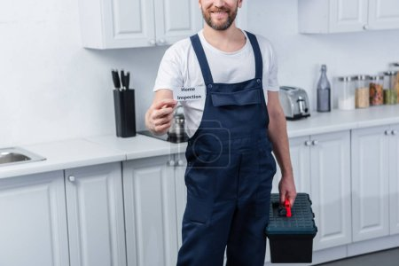 partial view of male handyman holding toolbox and showing card with lettering home inspection