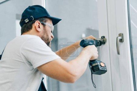 Photo pour Bricoleur dans des lunettes de fixation poignée de fenêtre par perceuse électrique - image libre de droit