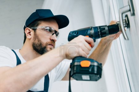 adult repairman in goggles fixing window handle by electric drill