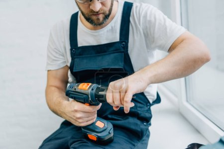 partial view of male handyman with electric drill sitting on windowsill