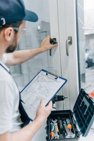 Foto de Vista parcial de manitas en gafas sosteniendo portapapeles y revisión identificador de ventana - Imagen libre de derechos