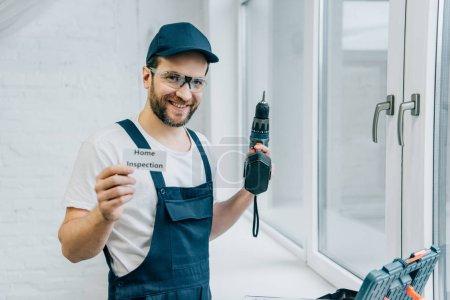 glücklicher erwachsener männlicher Handwerker hält Elektrobohrer in der Hand und zeigt Karte mit Schriftzug Home Inspection