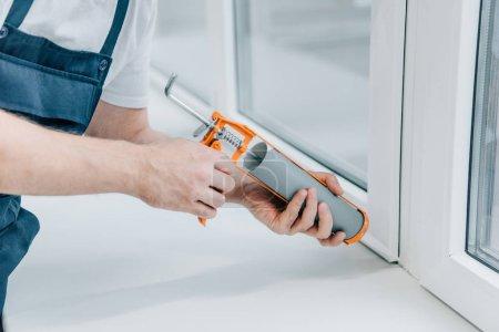 Photo pour Cropped image d'homme réparateur fixation fenêtre avec pistolet à mastic - image libre de droit