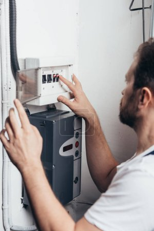 selective focus of male bearded handyman checking electrical box