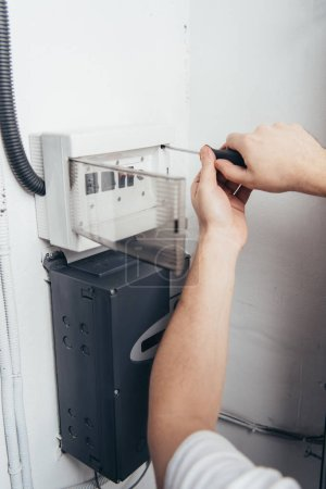 partial view of male electrician repairing electrical box by screwdriver